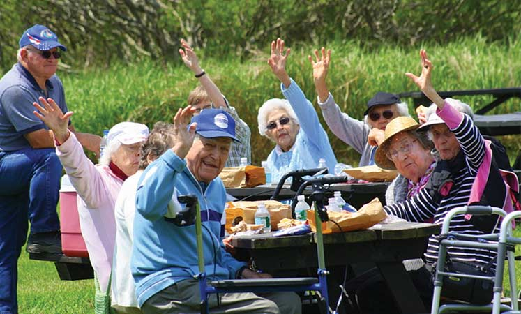 Ten seniors waving hello while sitting at a picnic table with food on it.